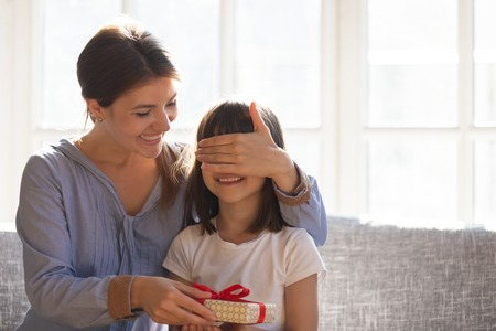 Smiling young loving mother cover daughter eyes with hand give her surprise, family celebrating child birthday holiday life event feels excited and happy, gift box as symbol of love care and attention