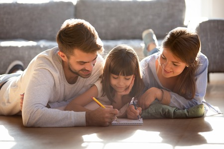 Married couple and small adorable daughter lying on wooden warm floor at modern home drawing on paper album with colored pencils. Having fun, child development, family leisure activity hobby concept