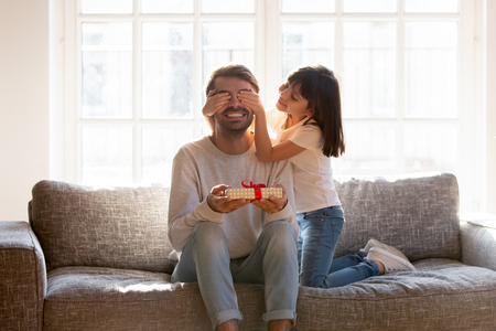 Small daughter congratulate daddy with father day, people sitting on sofa kid covering dad eyes with hands prepare for him gift box with surprise. Life events celebrating, love and attention concept