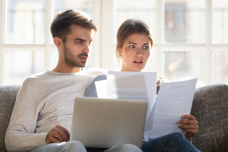 Couple sitting on couch at home use pc reading letter contract conditions terms feels stressed receive notice from bank account balance having due debt, check unpaid bills, financial problems concept 스톡 콘텐츠 - 120532137