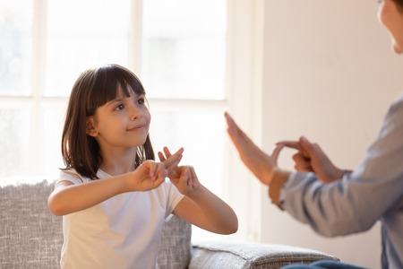 Mamá se comunica con su hija sorda y se enfoca en el niño sentado en el sofá en la sala de estar y hace que los dedos formen las manos hablando de manera no verbal. Concepto de escuela de aprendizaje de lenguaje de señas persona sorda discapacidad auditiva