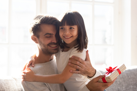 Happy family sitting on couch, loving dad cuddle little daughter showing sincere emotions love gratitude for gift, kid congratulate daddy with father day or birthday. Life events celebrations concept