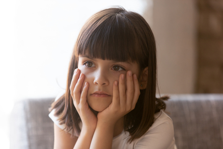 Cute lonely little orphan girl sitting on couch alone adoption childship and foster concept. Preschool depressed daughter feels unsure concerned hiding problems, psychological trauma, secretive child