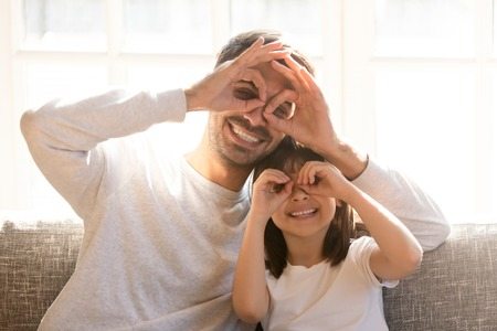 Pretty family father adorable daughter sitting on sofa do funny faces making with fingers eyewear shape like glasses looking through binoculars, have fun with child free time play tricks fool concept 版權商用圖片 - 120532153