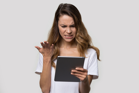 Millennial irritated woman pose over grey background, studio shot., female looking at tablet screen feels angry and frustrated having problems with gadget, received unpleasant message bad news concept Foto de archivo