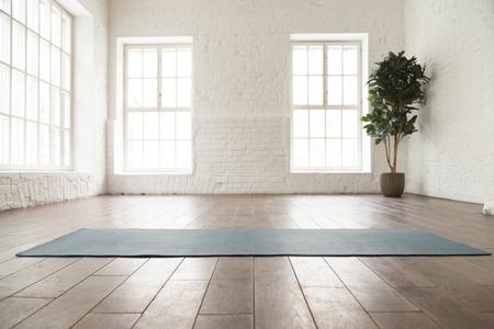 Abgerollte Yogamatte auf Holzboden im modernen Fitnesscenter oder zu Hause mit großen Fenstern und weißen Ziegelwänden, bequemer Platz für Sportübungen, Meditation, Yoga-Ausrüstung