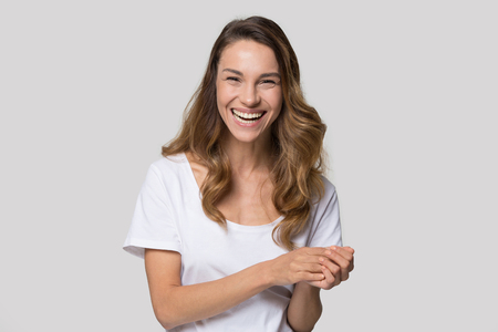 Laughing millennial woman posing over white wall background looking at camera feels overjoyed happy, head shot portrait. Concept of positive news, rejoice facial expressions, having fun and happiness