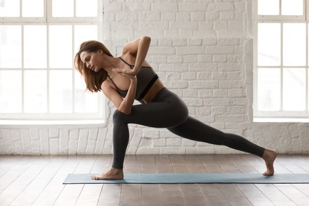 Young attractive woman practicing yoga, beautiful girl in grey sportswear, pants and bra standing in Parsvakonasana pose, Side Angle exercise, working out at home or in yoga studio with white walls Standard-Bild - 120532224
