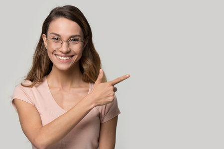 On grey wall background positive smiling female in glasses looking at camera pointing finger aside at copy space, client recommending eyewear great offer store, freespace for your advertisement text