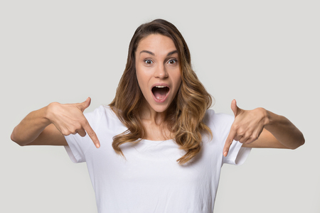 Head shot studio portrait surprised attractive woman open mouth make big eyes pointing index fingers down looking at camera on grey background, advertise new product or showing drop in prices concept Stock Photo