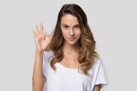 Disparo a la cabeza retrato mujer bonita con camiseta blanca mirando a la cámara se siente confiada mostrando el gesto ok hacer los dedos en forma de círculo, cliente satisfecho concepto de recomendación de retroalimentación positiva del cliente