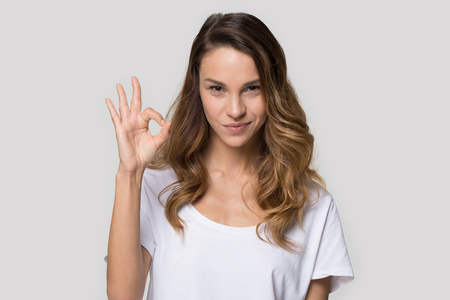 Head shot portrait pretty woman wearing white t-shirt looking at camera feels confident showing ok gesture make fingers circle shape, satisfied client customer positive feedback recommendation concept