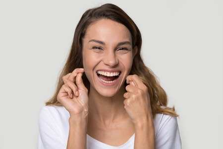 Beautiful smiling woman cleaning teeth with dental floss remove food between tooth preventing gingivitis and caries diseases, take care oral hygiene, concept image gray background studio shot portrait Archivio Fotografico - 120565889