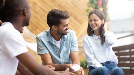 Persone felici multiculturali che ridono di uno scherzo divertente che parlano alla riunione della riunione sulla terrazza del caffè all'aperto, allegri amici diversi che si divertono bevendo caffè godono di risate, ritrovo di amicizia multietnica