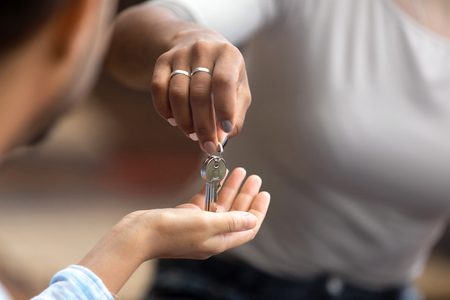 Close up view of female realtor agent broker hand giving keys to new house to male customer renter buyer tenant owner making real estate deal buy flat property concept, mortgage investment contract Standard-Bild - 120565895
