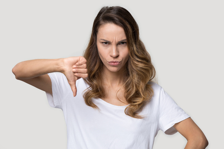 Angry frown facial expressions young attractive woman standing studio shot showing thumb down gesture symbol of disapproval negative feedback, dislike and rejection, confrontation disagreement concept Foto de archivo - 120572167