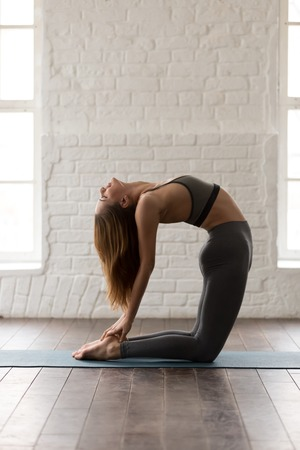 Young attractive woman in grey sportswear, pants and bra practicing yoga, beautiful girl standing in Ustrasana pose, Camel exercise, working out at home or in yoga studio, vertical photo Stock Photo