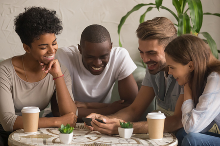 Multi-ethnic happy young friends group laugh watching funny online video on smartphone having fun together, diverse students looking at cellphone use mobile apps technology at meeting in coffee house