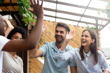 Happy multicultural young people friends group laugh give high five celebrate multi-ethnic friendship engaged in reunion cafe meeting, excited diverse students join hands show unity promise support Stock Photo