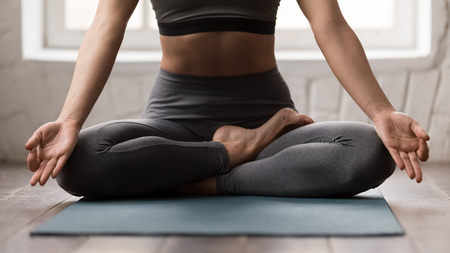 Schöne junge Frau, die Yoga praktiziert, in Padmasana-Pose auf der Matte sitzt, Lotus-Übungen macht, sportliches Mädchen in grauer Sportbekleidung, Leggings und BH, das zu Hause oder im Yoga-Studio aus nächster Nähe trainiert