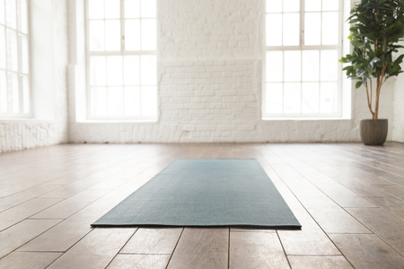 Empty room in yoga studio with unrolled yoga mat on wooden floor, modern fitness center with big windows and white brick walls, sport equipment for meditating or sport exercises close up