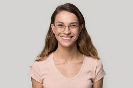 Head shot portrait woman with snow-white smile wearing glasses looking at camera, pretty female advertise good offer optics store or teeth whitening in dental clinic grey copyspace for your ad concept