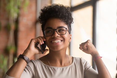 Excited overjoyed african american woman winner talking on the phone happy about good news, ecstatic mixed race girl speaking by cellphone celebrating success win victory, got new job opportunity