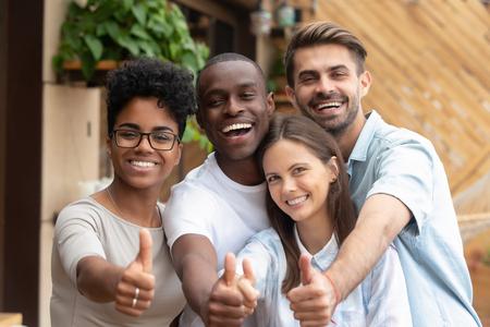 Joyeux groupe d'amis multiethniques montrant les pouces vers le haut, souriant divers jeunes regardant la caméra avec le même geste recommandent l'égalité de la diversité raciale de bonne qualité, l'amitié multiraciale, le portrait