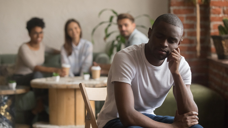Upset lonely african american man suffering from bullying racial discrimination mocking racism social rejection sitting alone, sad depressed black outstand loser guy hurt excluded by diverse friends