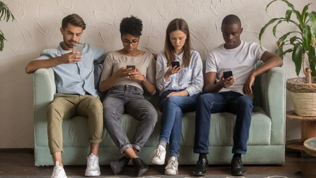 Multicultural young people using smartphones ignoring each other sitting in row on sofa, diverse millennial students obsessed with modern gadgets, mobile addiction, devices dependence overuse concept