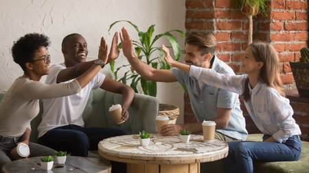 Happy multicultural young people group giving high five at coffee house meeting laugh celebrate multi-ethnic friendship, smiling diverse friends students teenagers team fun bonding together in cafe Stock Photo