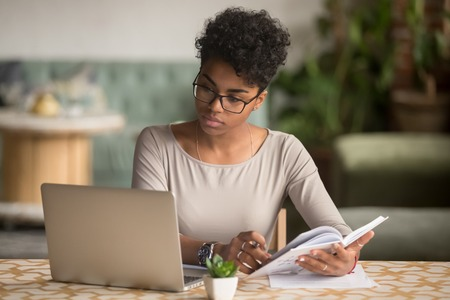 Focused young african american businesswoman or student looking at laptop holding book learning, serious black woman working or studying with computer doing research or preparing for exam online Stock Photo