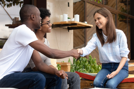 Happy african family couple clients customers handshake caucasian insurer saleswoman realtor making sale purchase deal agreement, renters customers shake hand of agent broker take loan, buy insurance Stock Photo