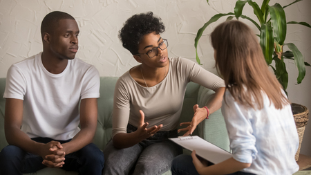 Unhappy jealous mixed-race wife talk to psychologist counselor complain on bad relationship with husband, african american family couple counseling have conversation about problem at therapy session Stock Photo