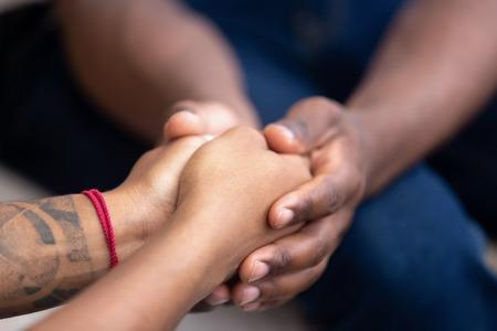 Amico dell'uomo di colore che tiene per mano la donna africana, la coppia della famiglia americana dà supporto psicologico, aiuta la fiducia cura empatia speranza nelle relazioni matrimoniali, concetto di onestà comfort, vista ravvicinata