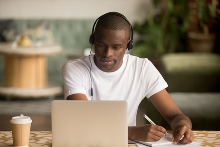 Focused african man wearing headphones watching webinar training making notes study online learning language on computer, black male student looking at laptop elearning in internet write information