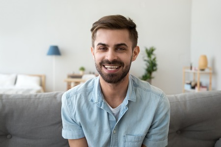 Head shot portrait of smiling happy man looking at camera, making video call, talking with friend, sitting on cozy coach at home, male vlogger recording webinar, communicate, broadcast live Stock fotó - 120572406