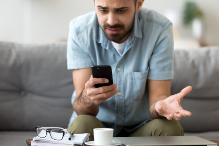 Close up confused man having problem with broken not working phone, annoyed frustrated male student receiving bad news, reading unpleasant email, sitting on sofa, looking at screen, spam message