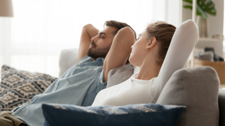 Peaceful man and woman relaxing leaning back with hands behind head on sofa in living room at home, young couple resting with closed eyes, dreaming, husband and wife taking nap, side view Banco de Imagens