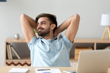 Satisfied student, businessman relaxing leaning back with hands over head after finished work at workplace, break, smiling man received good online news, email, excited by business success