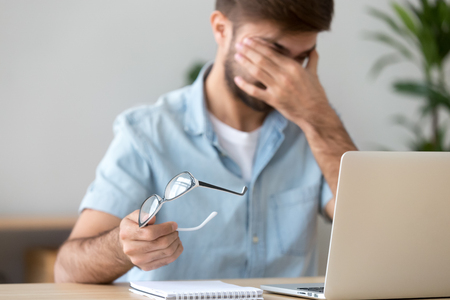 Tired man suffering from dry eyes syndrome after long computer work, taking off glasses, exhausted student or freelancer sitting at workplace with laptop, massaging eyelids, health problem