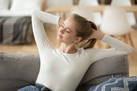 Happy calm woman relaxing, stretching hands on comfortable sofa at home, enjoying weekend, free time, pleasant lazy day, no stress concept, carefree satisfied girl doing easy exercise