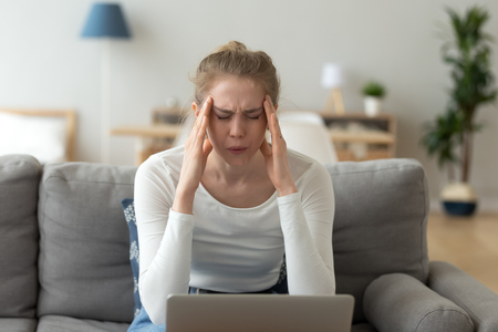 Upset woman suffering from headache, touching temples, breathing deep, feeling pain, sitting on sofa in living room, overworked, difficult computer work, online project, having health problem