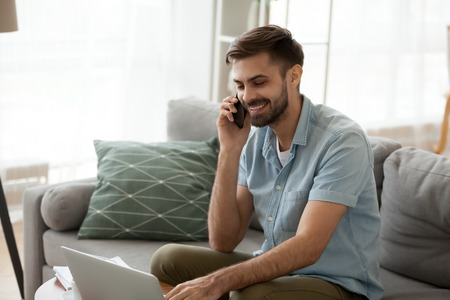 Smiling happy man using laptop and talking on phone at home, having pleasant conversation with friend or client, typing, satisfied student holding smartphone in hand, sitting in living room on sofa