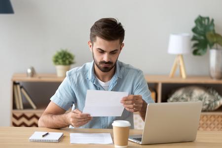 Homme d'affaires sérieux et concentré, pigiste lisant attentivement un document papier, nouvelles désagréables, lettre reçue, analyse de l'offre, rapport financier avec statistiques du projet, notification