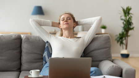 Peaceful satisfied woman stretching with hands behind head after finish computer work on cozy sofa in living room, taking break, breathing, sleepy girl with closed eyes having rest at home