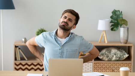 Tired man feeling backache after sedentary computer work, suffering from pain, exhausted student or freelancer massaging back in uncomfortable posture in office, sitting at workplace
