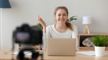 Happy smiling woman sitting at desk, recording video in office or home, modern blogger, business coach sharing thoughts, good mood, successful freelancer making content, using digital camera Stock Photo