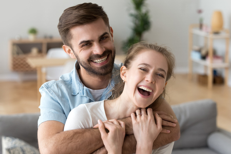 Head shot portrait of happy excited young couple in love at home, handsome smiling husband embracing, holding in hands attractive laughing wife, looking at camera, having fun together in living room 版權商用圖片