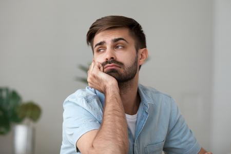 Müder, gelangweilter Mann, der in der Ferne schaut, zu Hause oder am Schreibtisch sitzt, schläfriger Freiberufler oder Student, der sich faul fühlt, keine Motivation hat, über einen monotonen Routinejob nachdenkt, Nahaufnahme